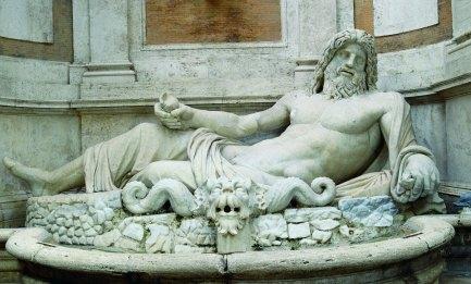 """Marforio Sdraiato sul fianco sinistro, volto reclinato, lunghi capelli e barba, la statua """"del Marforio"""" è davvero colossale (242 cm!). Conosciuto fin dal Cinquecento, molti studiosi vi individuano la raffigurazione del Tevere o di altra divinità fluviale pertinente anche in antico ad una fontana. Stilisticamente è attribuito all'Età Flavia (I secolo d.C.) ma divenne molto noto a partire dal Rinascimento perché fu utilizzato per affiggere """"pasquinate"""", scritti diffamatori contro il Governo, che i romani firmavano con il nome di """"Pasquino"""". PER CHI: Per chi ama tutti gli sport e soprattutto quelli acquatici DOVE: Puoi trovarlo nel cortile di Palazzo Nuovo, Musei Capitolini — presso Musei Capitolini."""